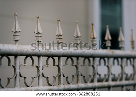 A white fence which has become rusted through years of neglect - stock photo