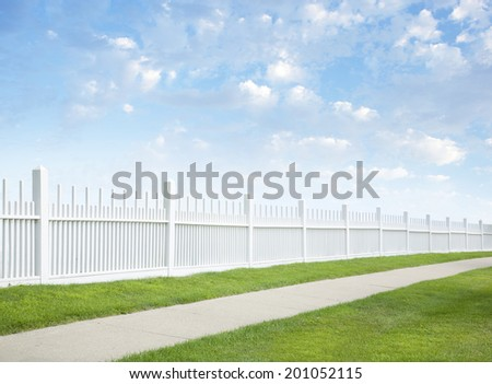 A white fence with grass and sidewalk beneath blue sky and clouds - stock photo
