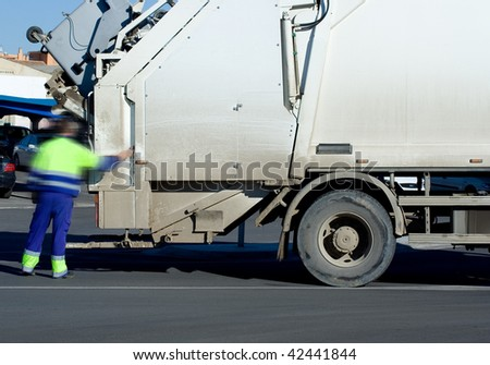 A White Garbage Truck with male worker - stock photo