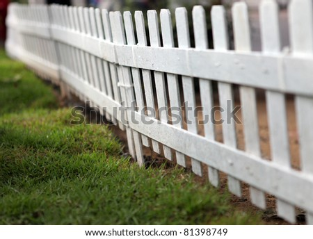 A White Gate and Fence with Grass Field