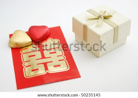 A white gift or jewelry box with two heart shape candy and a Chinese double happiness red packet.