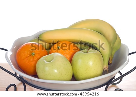A white glass bowl full of bananas, oranges and apples, shot on a wooden board