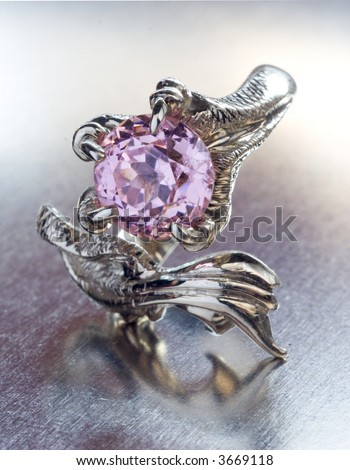 a white gold dragon ring with pink amethyst on metal background - stock photo