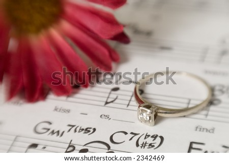 A white gold, vintage, diamond engagement ring sits on top of a piece of music with the word kisses shown in the lyrics next to the ring. - stock photo
