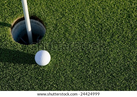 A white golf ball near the hole of a golfing green or course - stock photo