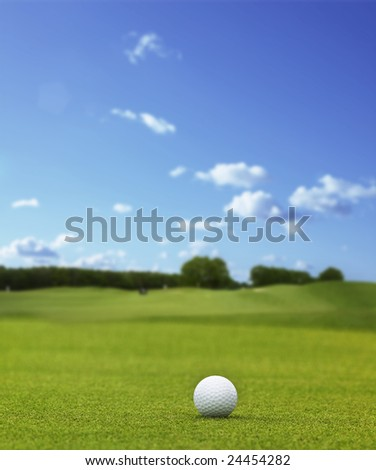A white golfball laying at a golf course under blue sky - stock photo