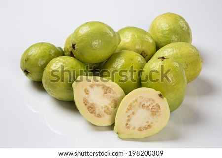 A white guava cut in a alf in front of some entire white guavas over a wooden surface on a white background.