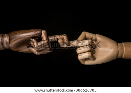 A white hand and black hand express respect, solidarity and aid in crossing their fingers. On black background. - stock photo