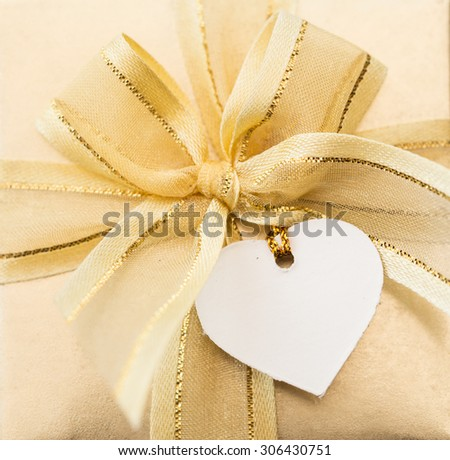 A white heart card on a gold ribbon gift box