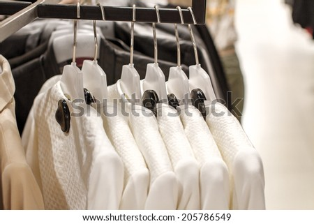 a white jackets hanging on a hanger in the store