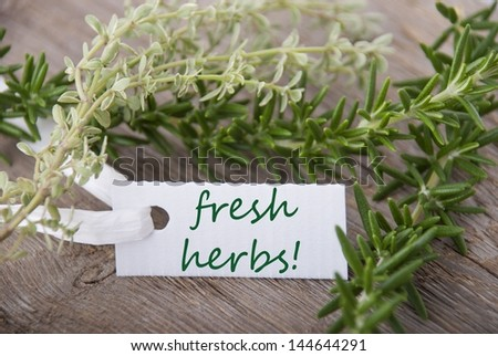 a white label with fresh herbs on it and herbs in the background - stock photo