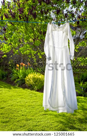 A white lacey vintage dress hanging on a cloths line with strong backlighting. - stock photo