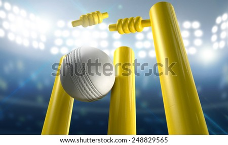 A white leather cricket ball hitting yellow wooden cricket wickets on a floodlit stadium background at night - stock photo