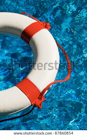 a white life ring with red stripes in the blue water. - stock photo