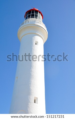 A white lighthouse with blue sky and red color on the top  - stock photo