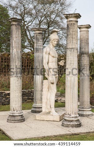 A White male, roman style stone carved statue, amongst stone carved pillars. - stock photo