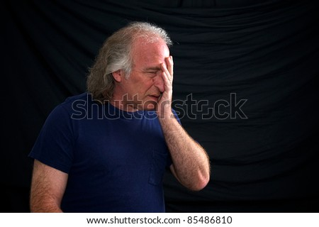 A white man is holding his head as if in despair, he looks upset or hurt against a black background and wearing a t shirt. - stock photo