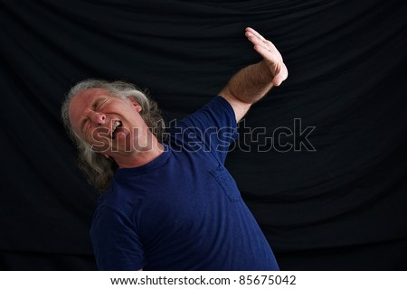 A white man is leaning back and has his hand up and head back with eyes closed and mouth open as if blocking an explosion or something dangerous.