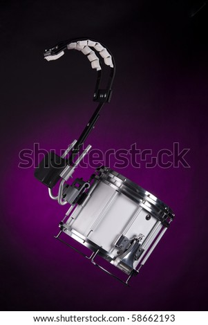 A white marching snare drum isolated against a spotlight purple background in the vertical format.