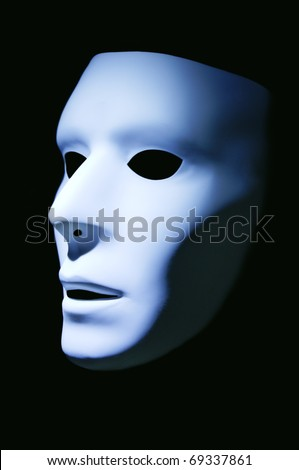 A white mask with a blue hue against a black background. - stock photo