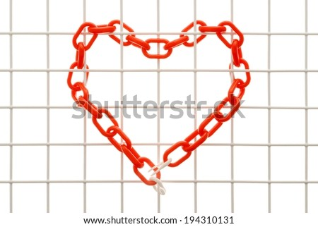 A white mesh with a red link chain woven between the grid in a heart shape. - stock photo