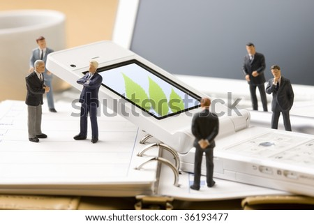 A white mobile phone surrounded by six models of  businessman - stock photo