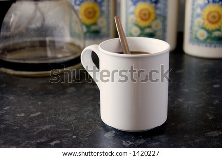 A white mug of coffee with a spoon - stock photo