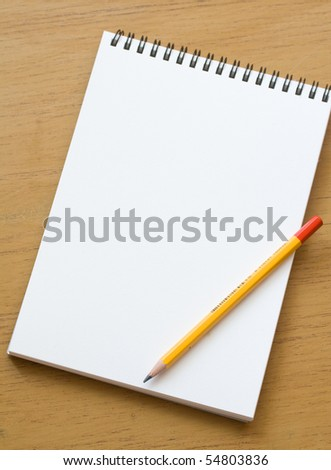 A white note book with lots of room for your text or image and a regular pencil on a wooden desk - stock photo