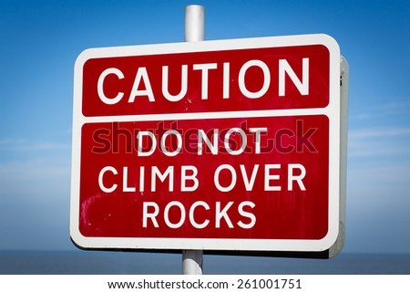"A white on red warning sign on the beach saying; ""Caution! Do not climb over rocks"". - stock photo"