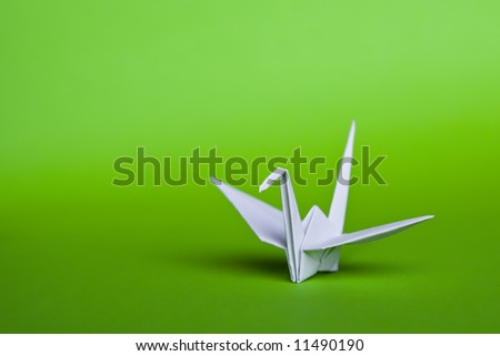 A white origami crane on a green background - stock photo