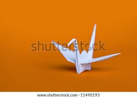A white origami crane on an orange background - stock photo