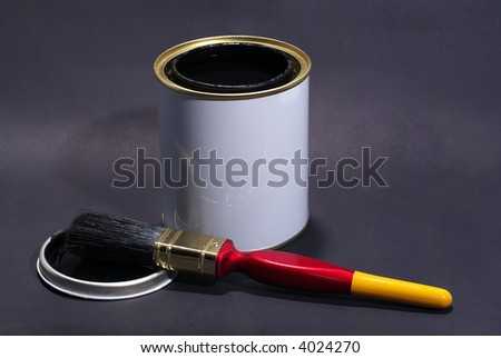 A White Paint tin containing black paint on a dark grey background with apaintbrush - stock photo
