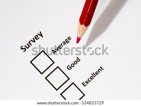 A white paper with choices and a red pencil. Survey asks the persons opinion whether it is average, good or excellent. The focus point is on the pen tip. - stock photo