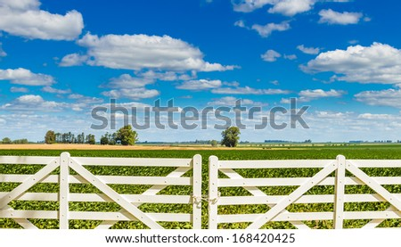 A white picket fence gate in front of a beautiful farmland on a sunny day