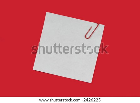 A white piece of paper with a red paperclip attached. - stock photo