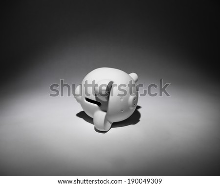A white piggy bank in the spotlight lying on its sad side. - stock photo