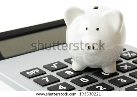 a white piggy bank on top of a calculator - stock photo
