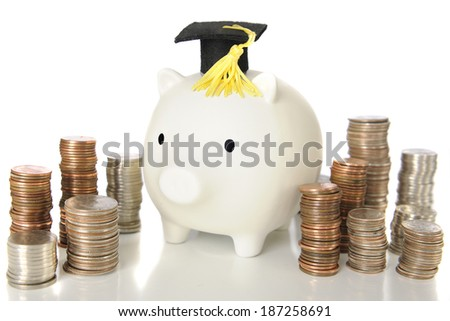 A white piggy bank wearing a graduation cap.  He's surrounded by stacks of shiny coins -- signifying college expense of potential new earnings.  On a white background.   - stock photo