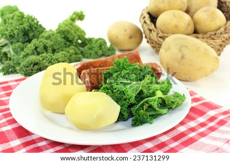 a white plate with kale and pee sausage - stock photo