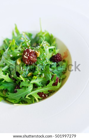 A white plate with rucola salad, seeds and berries, diet healthy snack