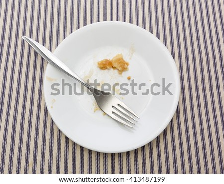 A white plate with the crumbs of a finished apple pile plus a fork to the side on a striped table cloth. - stock photo