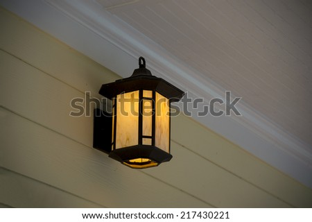 A white porch light against a brown vinyl siding - stock photo