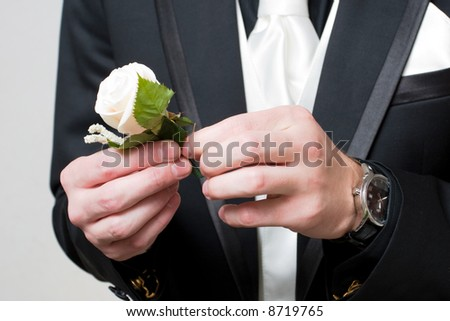 a white rose in the hands of the man in the black suit