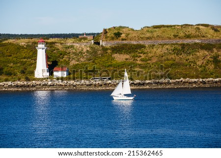 A white sailboat near white lighthouse on Canadian coast - stock photo