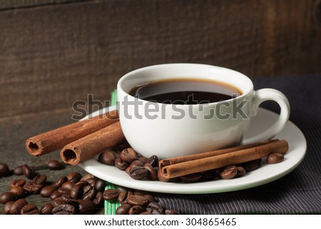 A white set of coffee on wooden and sacking background with cinnamon and coffee beans