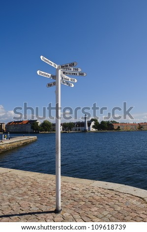 A white signpost in Karlskrona harbor, Sweden, showing distances to some of the most important cities of the Baltic Sea - stock photo