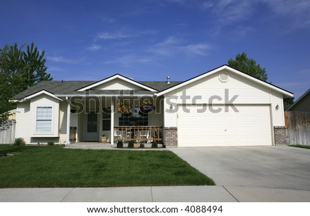 A white single level home under beautiful blue skys with hanging baskets of flowers and green lawn