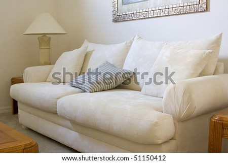 A white sofa with cushions in a living room of a residential home - stock photo