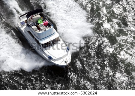 A white speedboat, with a very untidy upper deck, shot from above while travelling fast. - stock photo