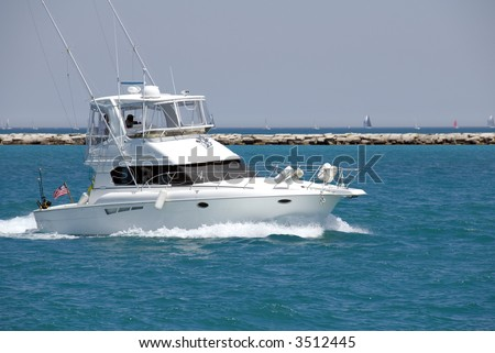 A White Sport Fishing Boat Flying The US Yacht Ensign Heads Towards Open